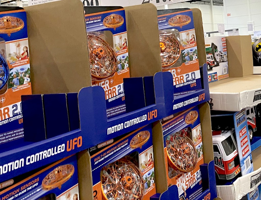 blue and orange ufo drone toys in blue boxes stacked at store