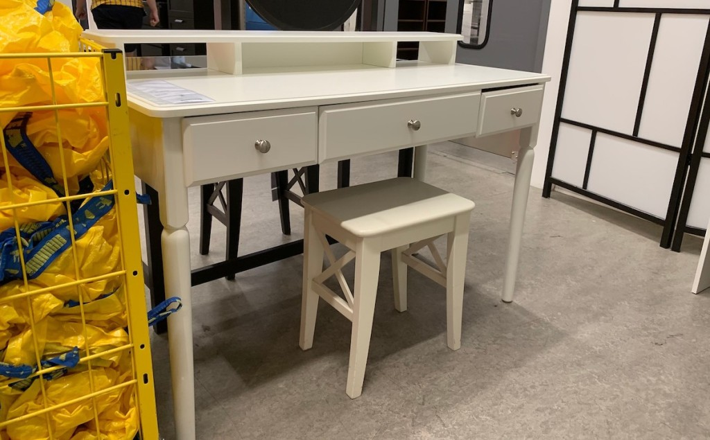 white vanity desk sitting in IKEA store with yellow bags