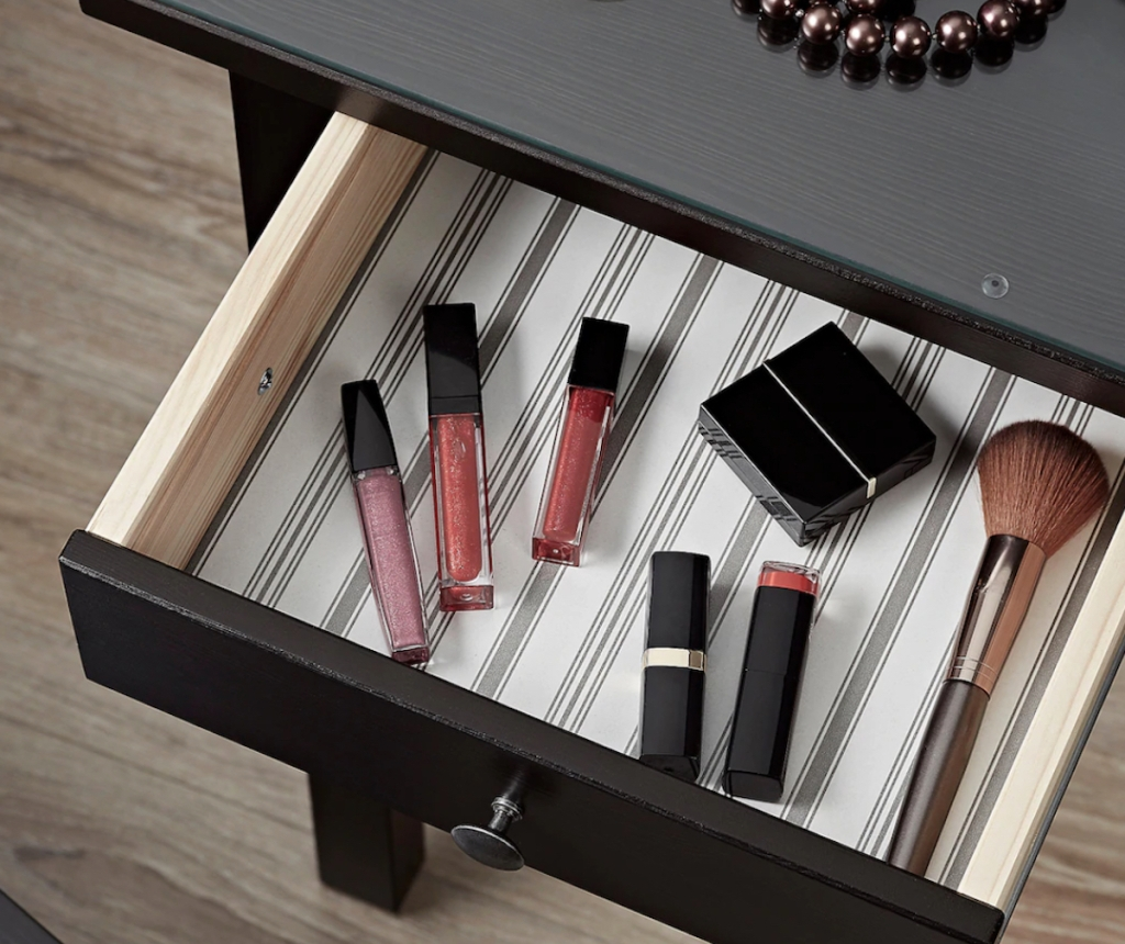 black brown vanity drawer filled with various makeup