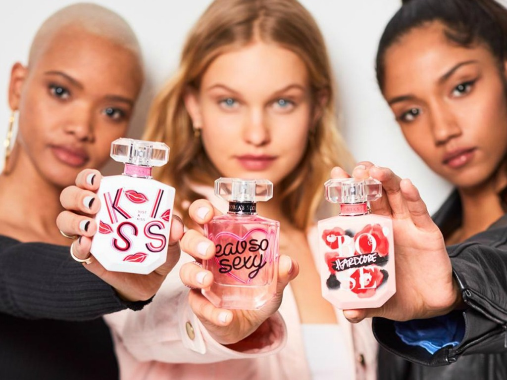 three women holding three bottles of perfume