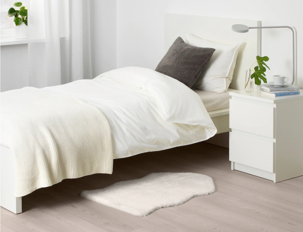 small white rug a foot of bed