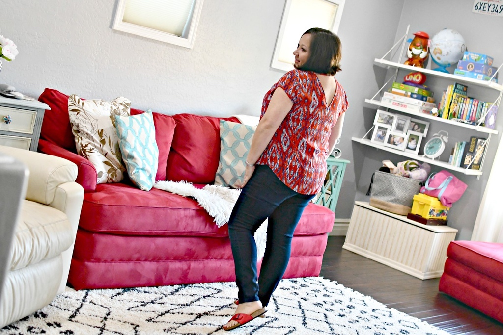 woman modeling the back of her skinny jeans in living room