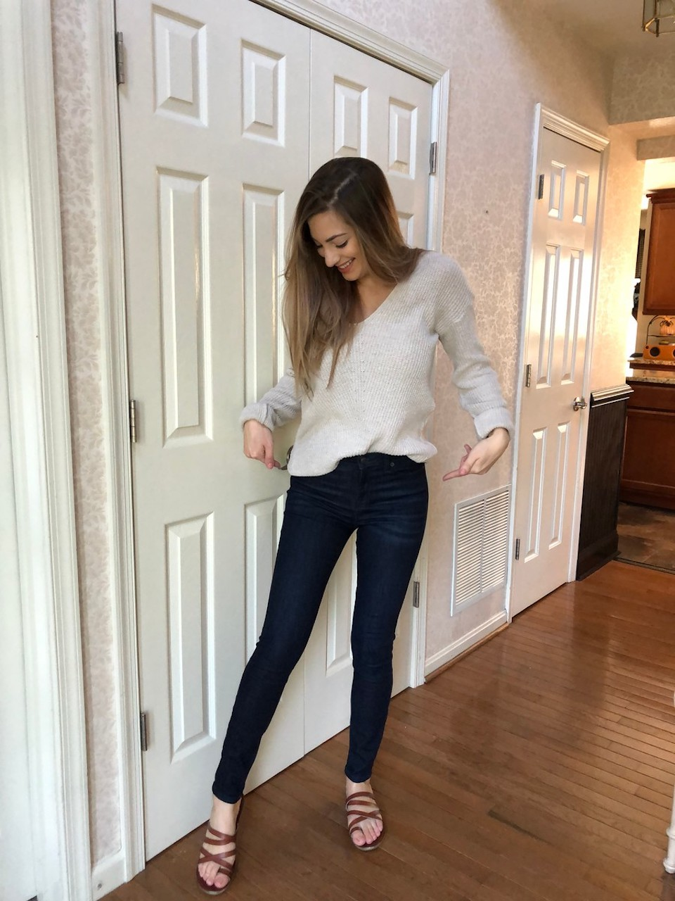 woman wearing skinny jeans with sweater and sandals