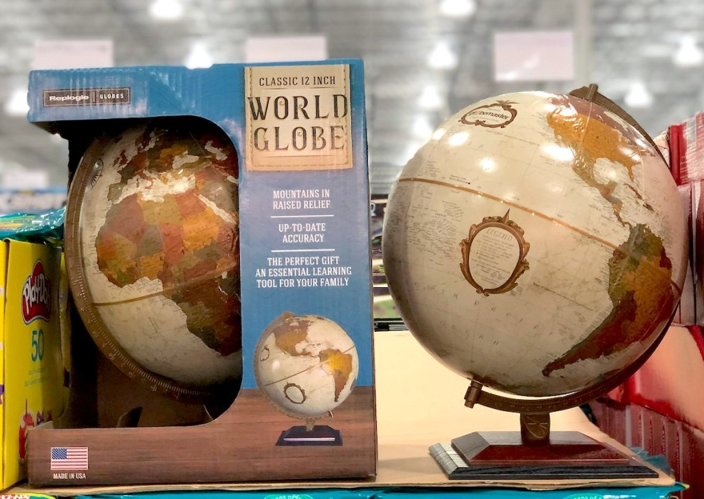 world globe sitting next to boxed toy at store with bright lights