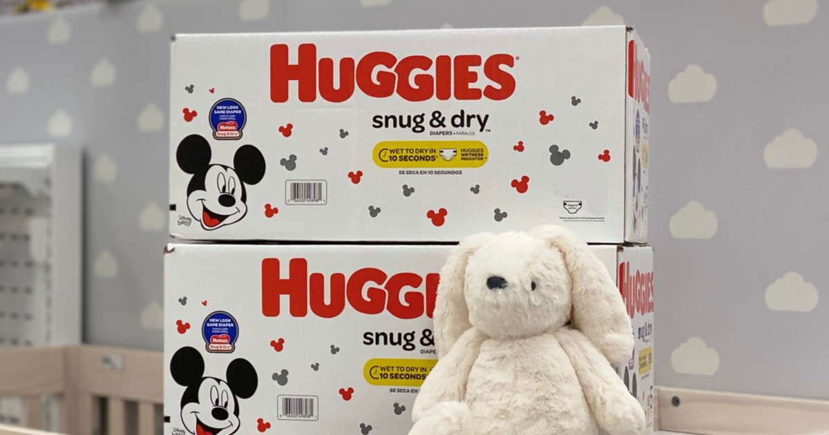 Huggies Snug & Dry Dry Diapers with bunny resting on boxes in nursery