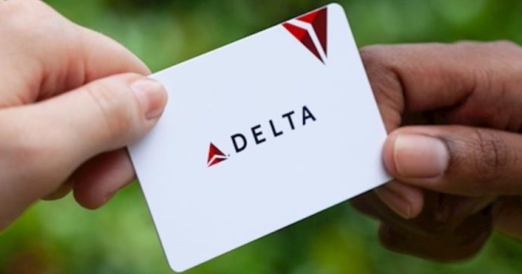 two hands holding Delta gift cards