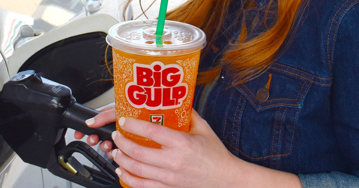 woman pumping gas and holding large orange fountain drink