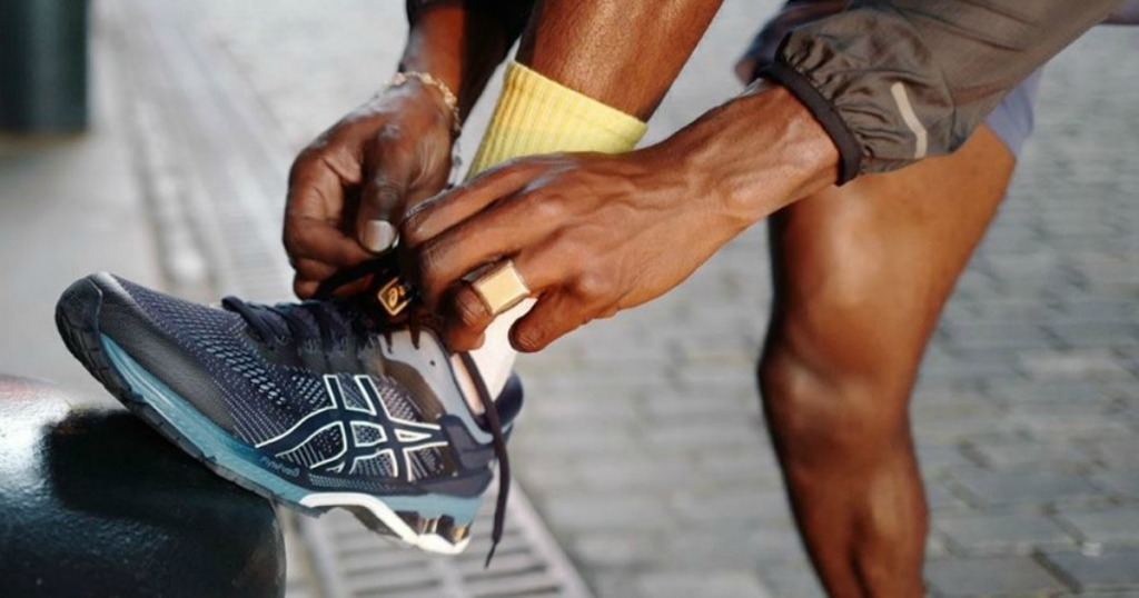 man lacing up a pair of ASICS Running Shoes
