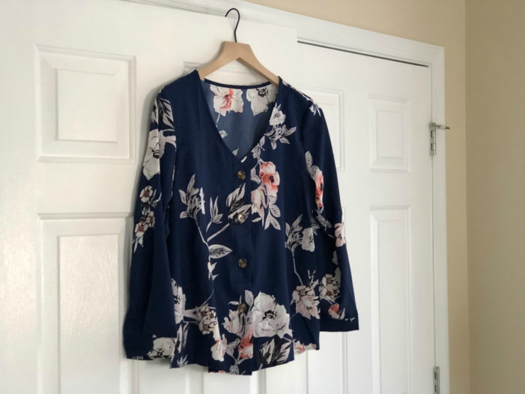 navy blue and floral shirt hanging on a door