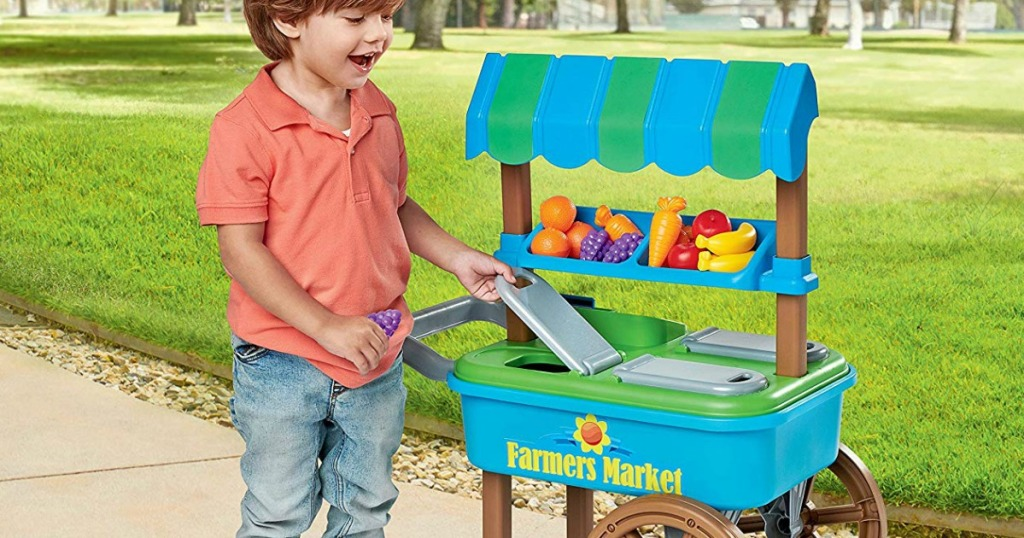 little boy playing with plastic cart and food toys