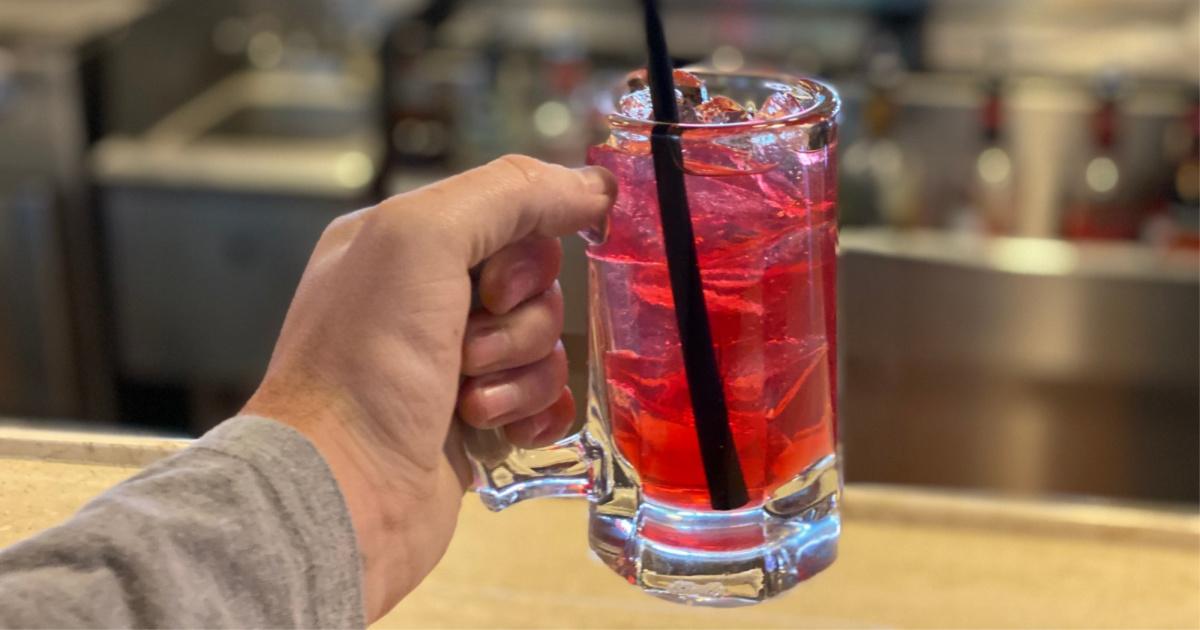 hand holding up mug of vodka cranberry lemonade drink