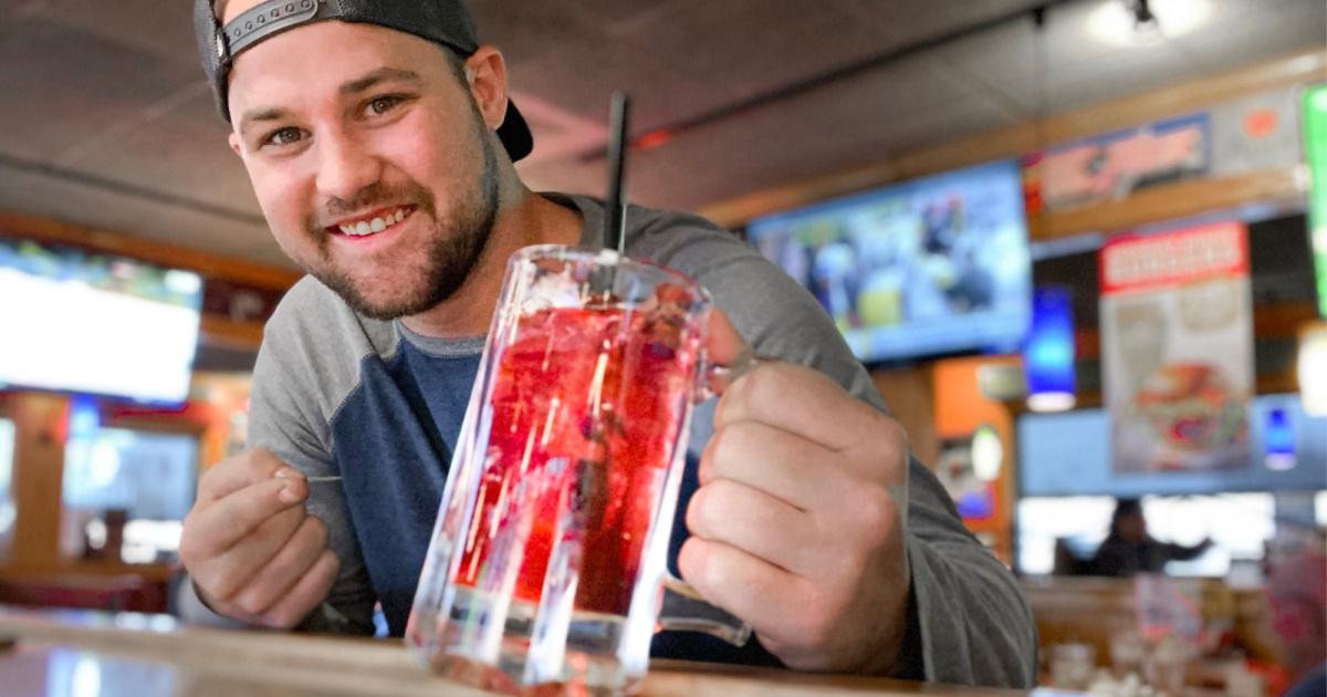 man holding up mug with vodka cranberry lemonade drink