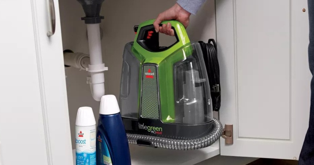 BISSELL Little Green ProHeat Portable Deep Cleaner being put away under the cabinet