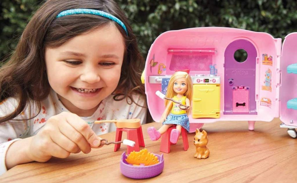 girl playing with Barbie Chelsea Camper