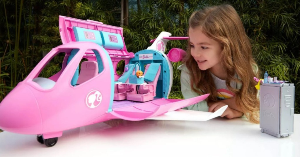 girl playing with Barbie Dream Plane