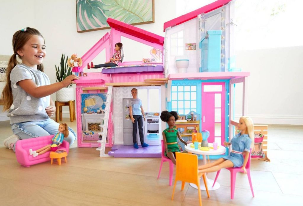 girl playing with Barbie Malibu House Doll Playset