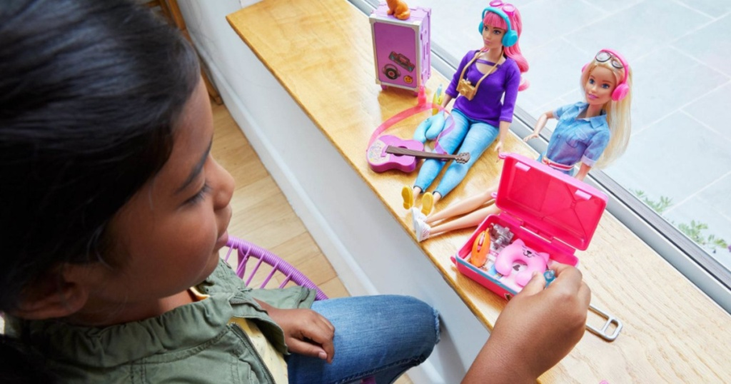 girl playing with barbie set