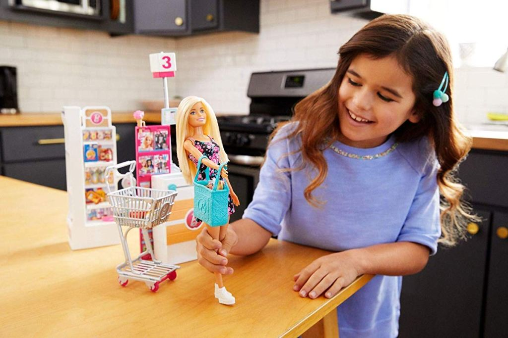 girl playing with Barbie Supermarket Playset