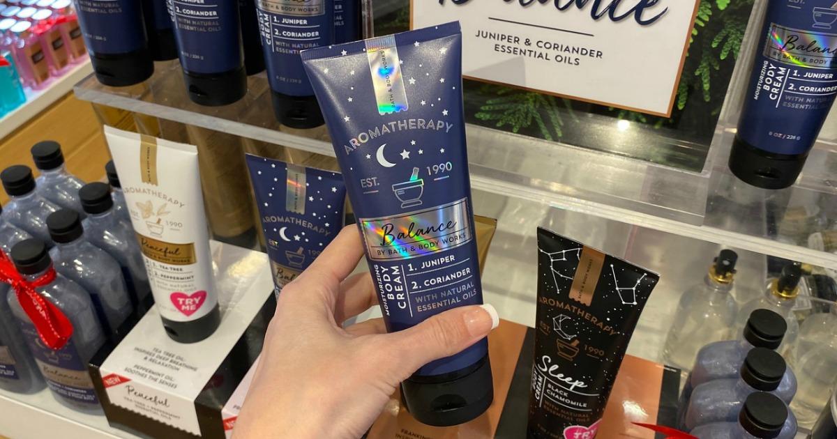 Hand holding Bath & Body Works Aromatherapy body cream in navy blue tube