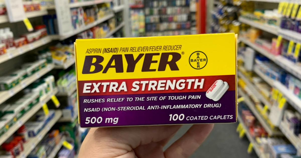 Hand holding Bayer in front of shelf