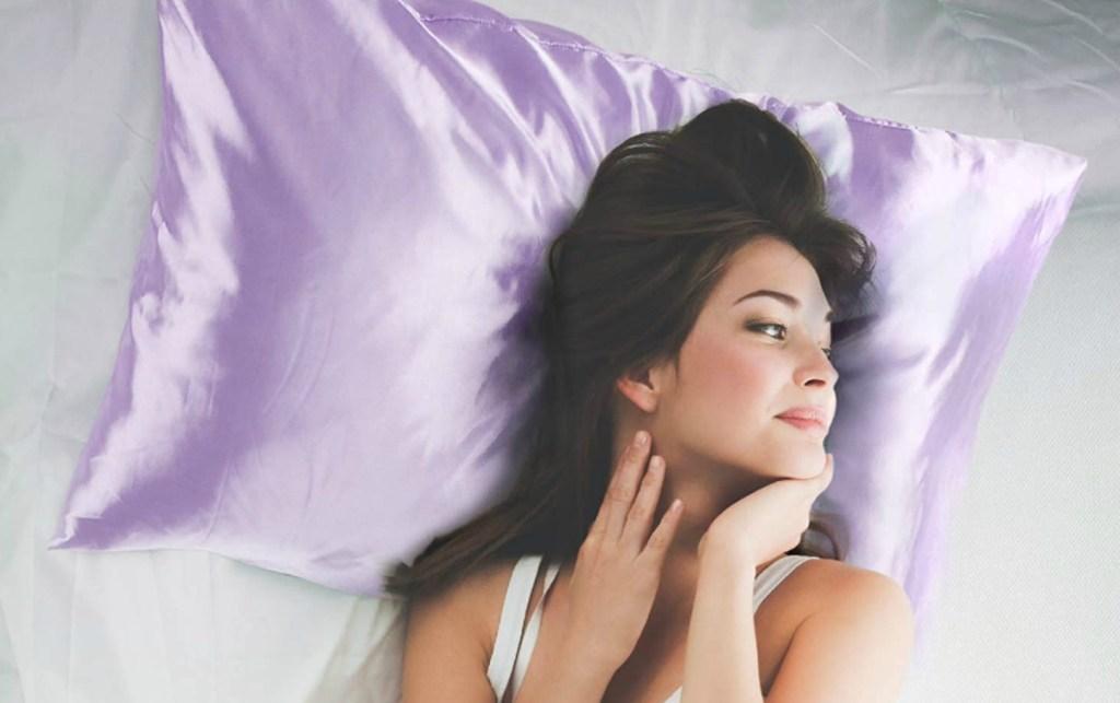 Woman laying on purple satin pillowcase