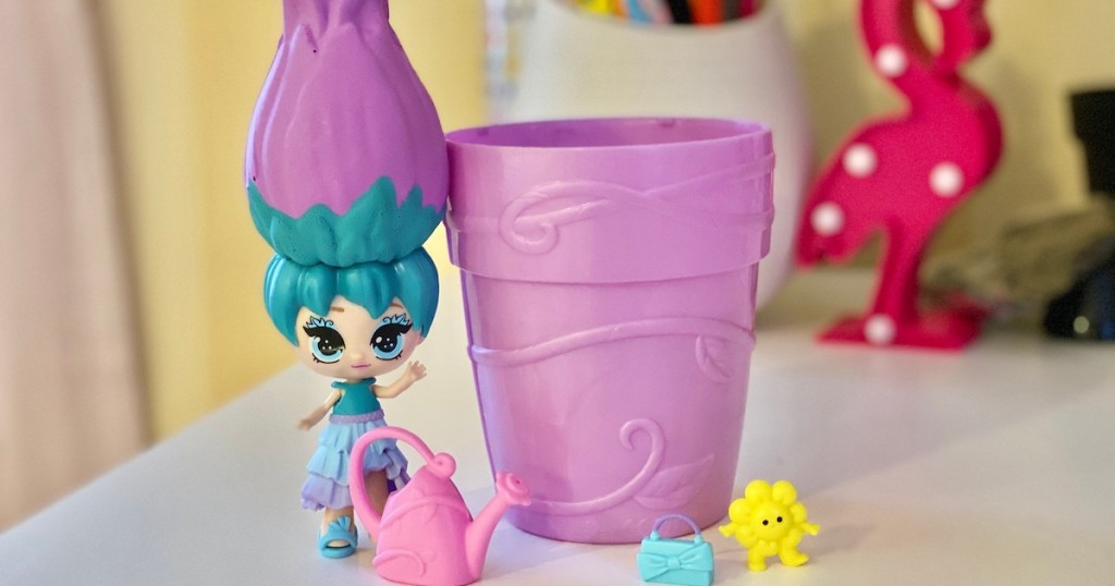 purple and blue doll standing on desk next to flower pot toy and accessories