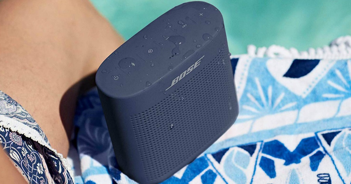 person sitting next to Bose SoundLink Speaker