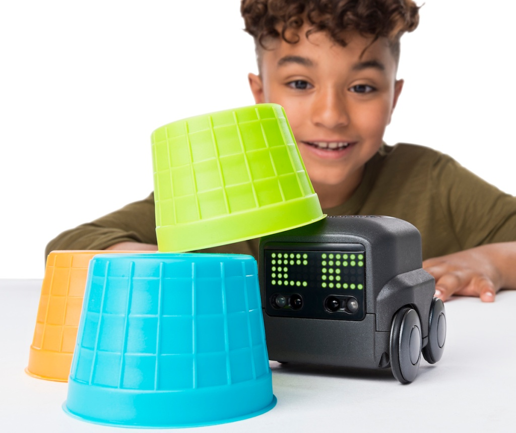 boy playing with Boxer Robot toy and stacking cups