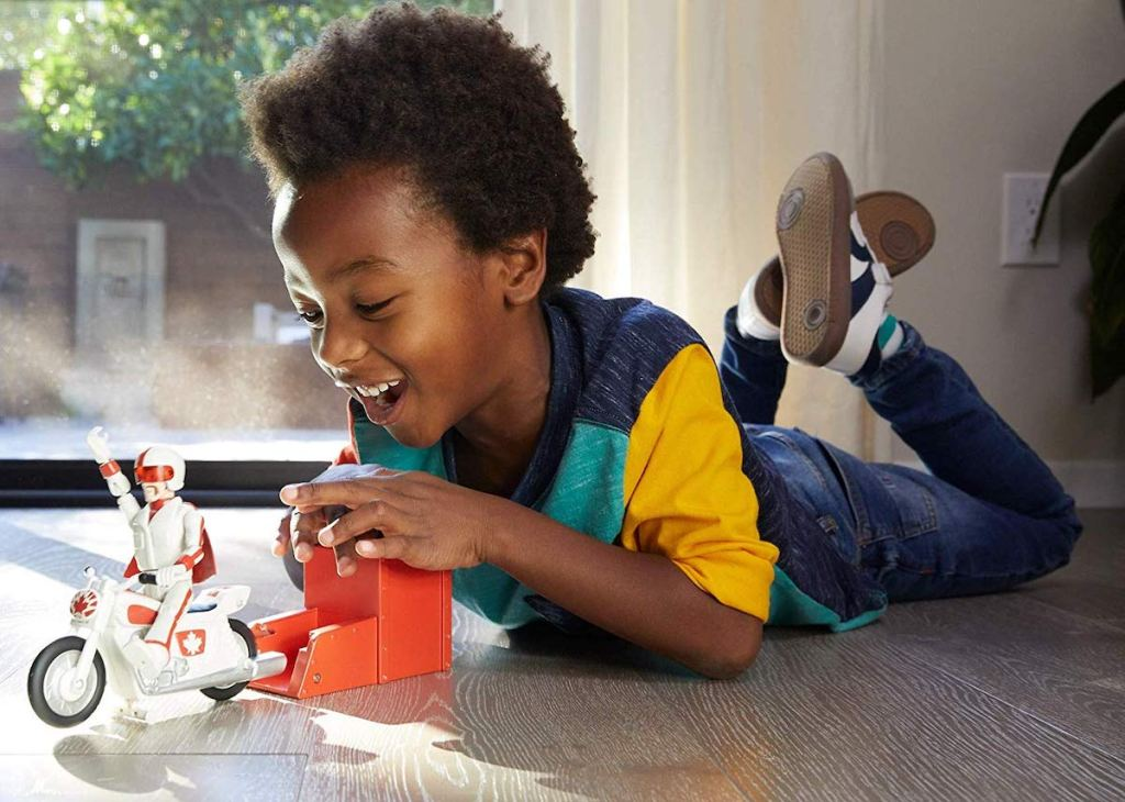 Boy playing with Disney Pixar Toy Story Stunt Racer Duke Caboom