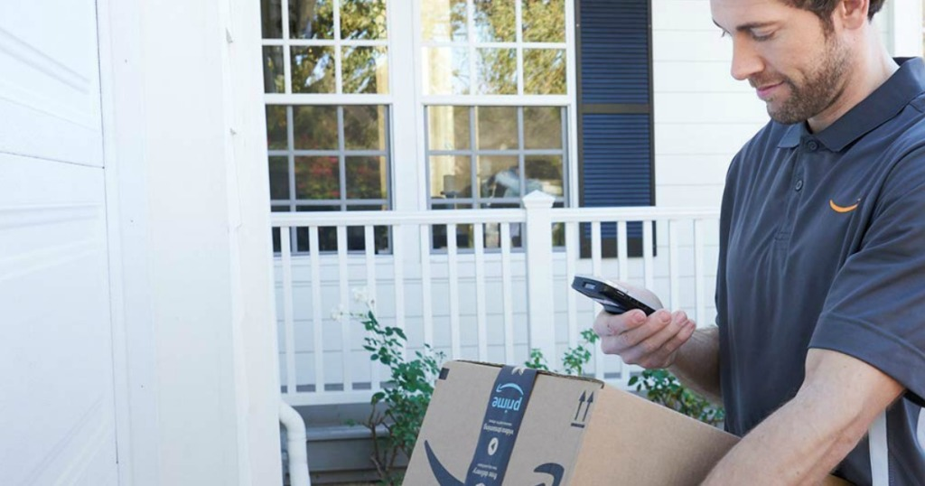 man checking smartphone while holding an Amazon box