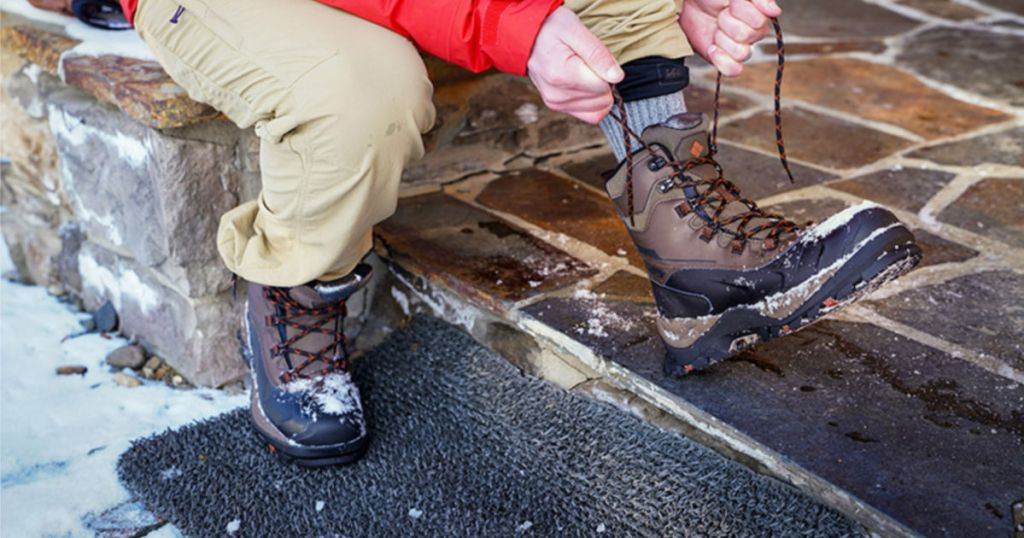 man tying Columbia Bugaboot Plus IV Omni-Heat Winter Boots in brown