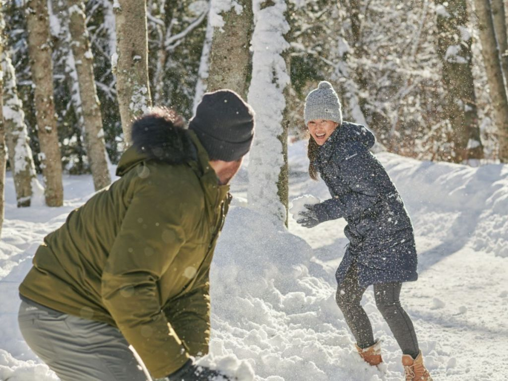 man and women having a snow fight wearing Columbia jackets