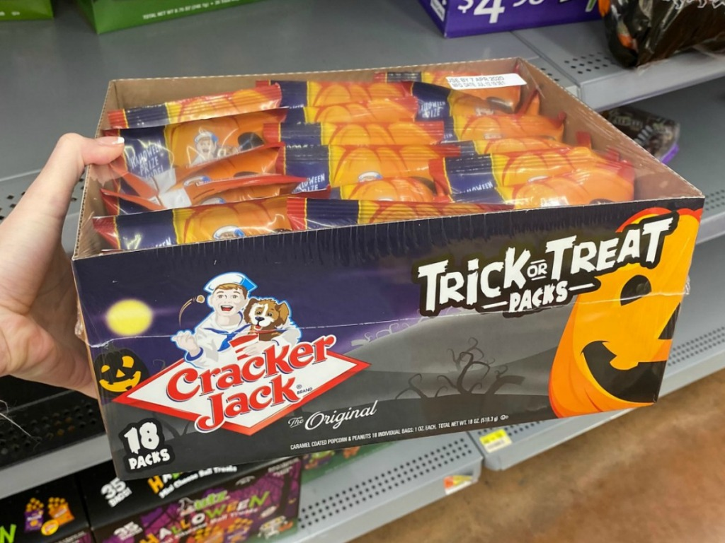 Hand holding Cracker Jack Trick or Treat Packs in store near Walmart shelf