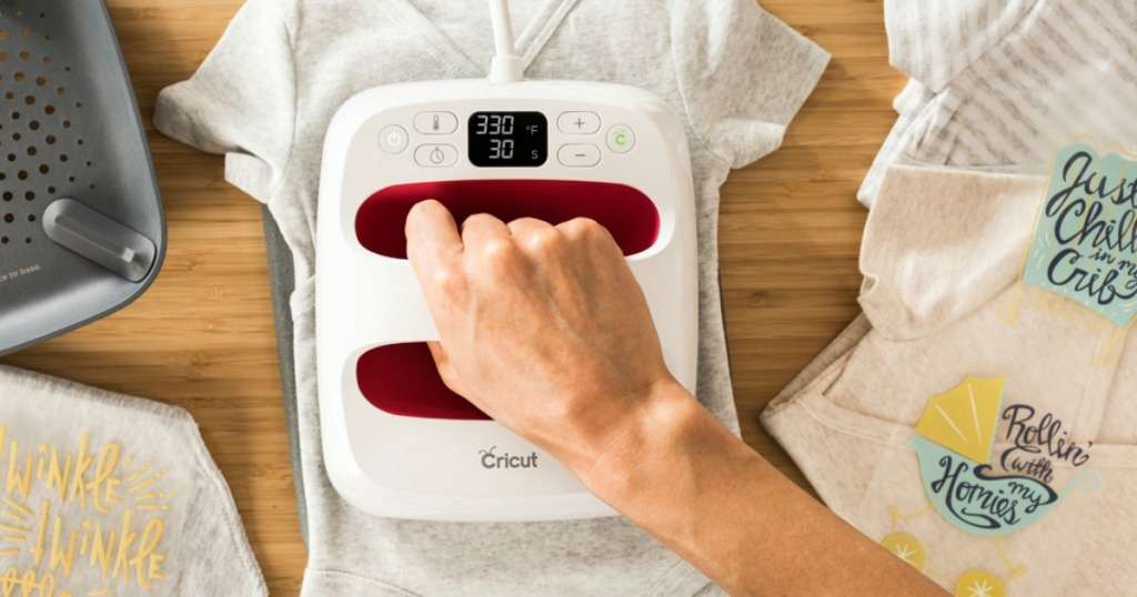 Person customizing baby bodysuit with Cricut Easy Press 2