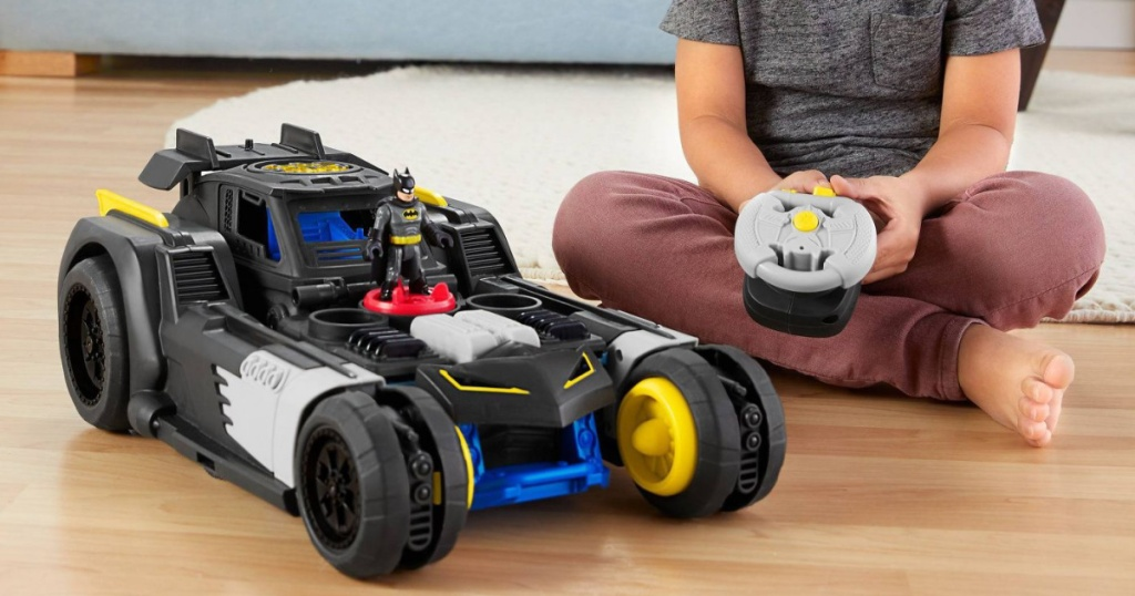 boy playing with a toy Batmobile car