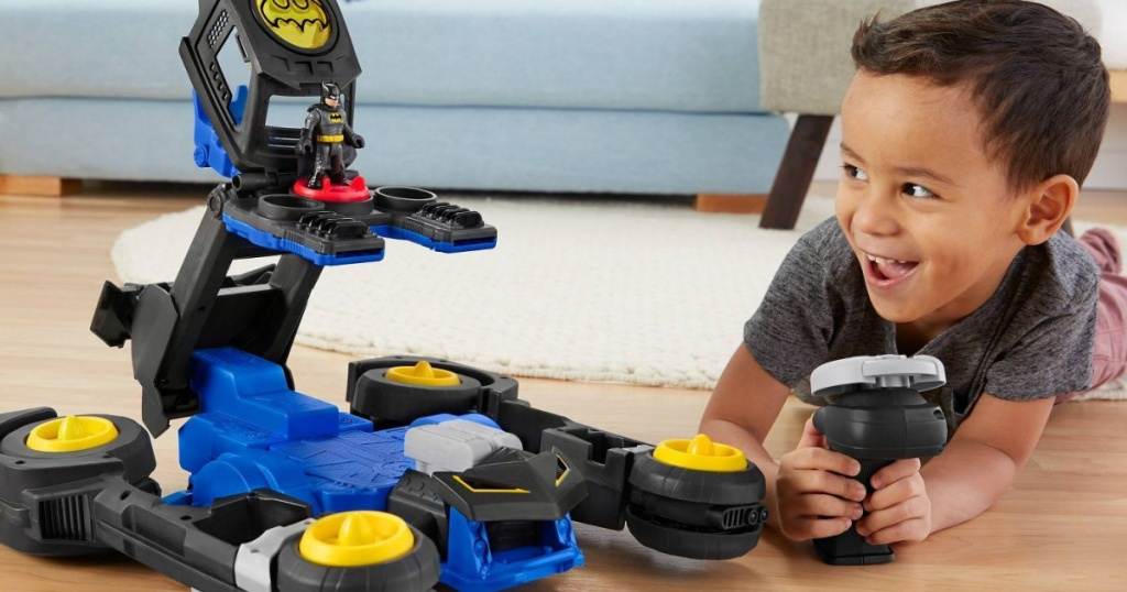 boy playing with dc super friends thransforming batmobile vehicle