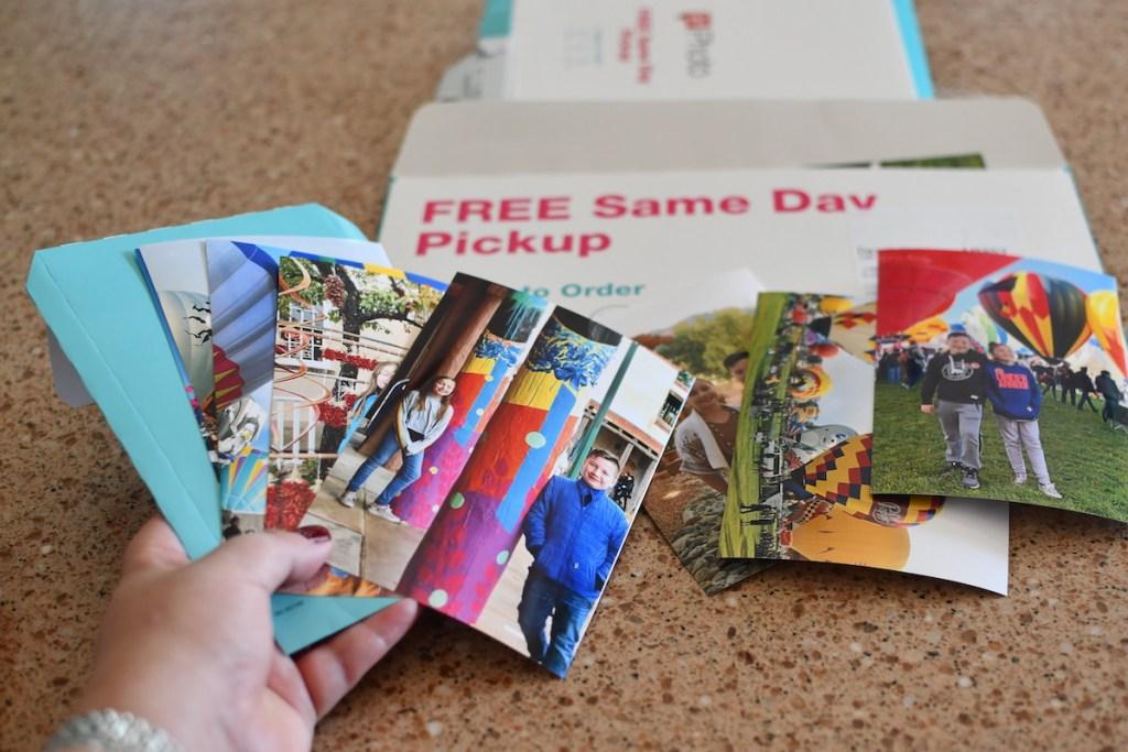 Woman holding several Walgreens photos