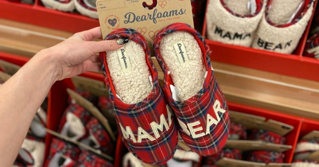 Woman holding a pair of red plaid Dearfoams Matching Slippers