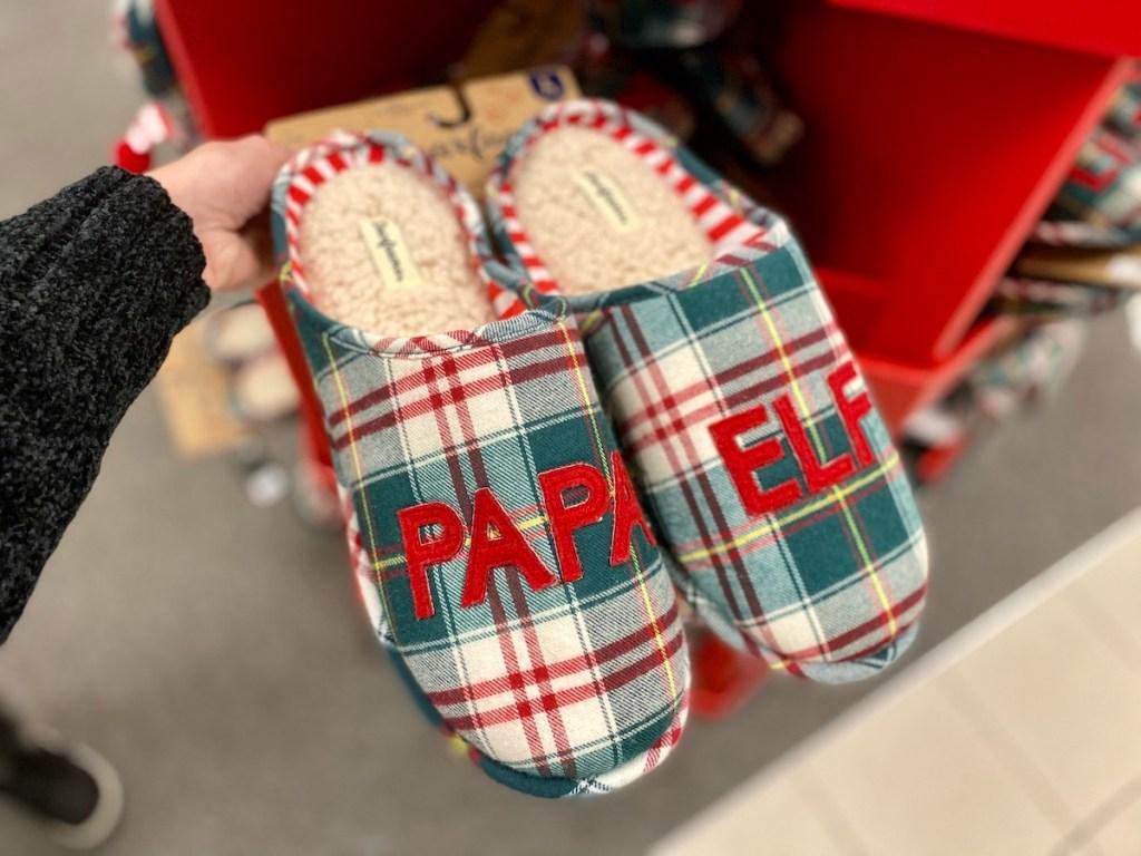 "Woman holding pair of Dearfoams Men's Matching ""Papa Elf"" Slippers"