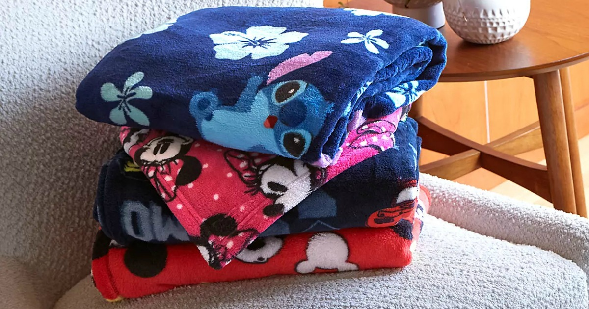 Disney Plush Blankets folded in stack on armchair