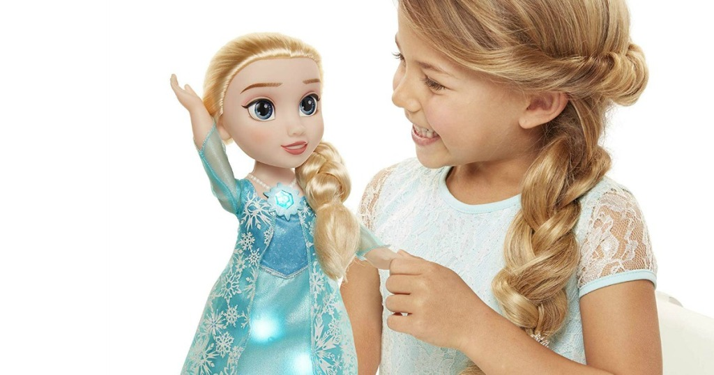 little girl playing with a Disney Frozen Snow Glow Elsa Doll