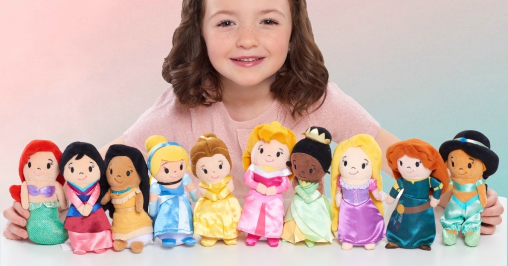 Young girl with a Disney Princess Plush Dolls collection on table top