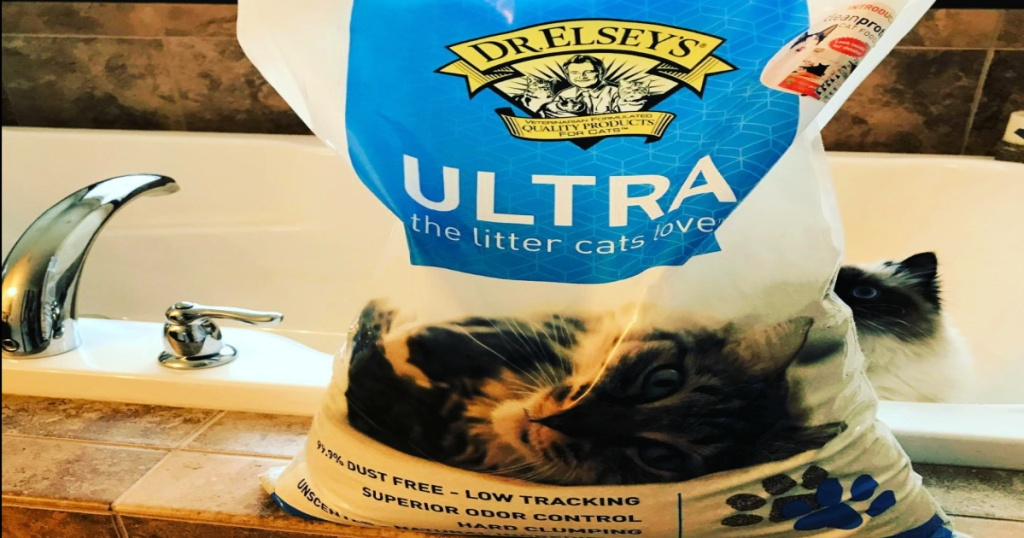 Dr. Elsey's Premium Clumping Cat Litter Bag on the side of a bath tub with white cat in the tub