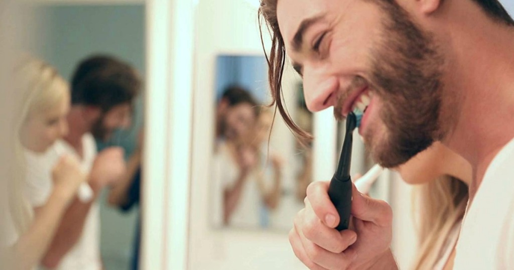 man brushing his teeth with a black electric toothbrush