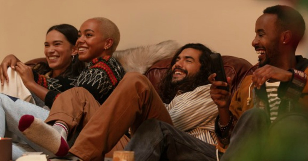 men and womn sitting on a couch watching tv and laughing