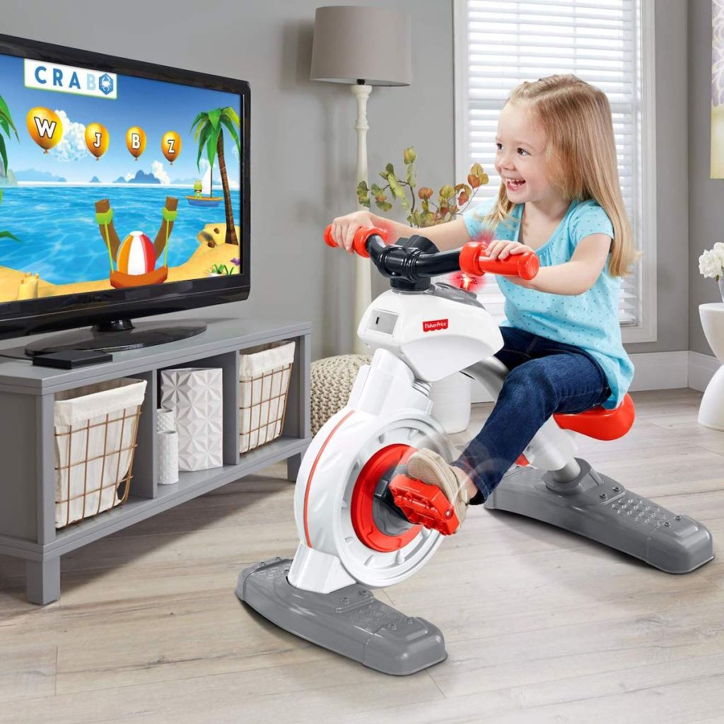 blonde girl riding on Fisher-Price Think & Learn Smart Cycle in living room with tv on