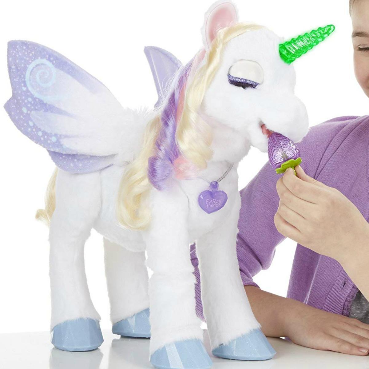 Girl feeding a plush unicorn a strawberry