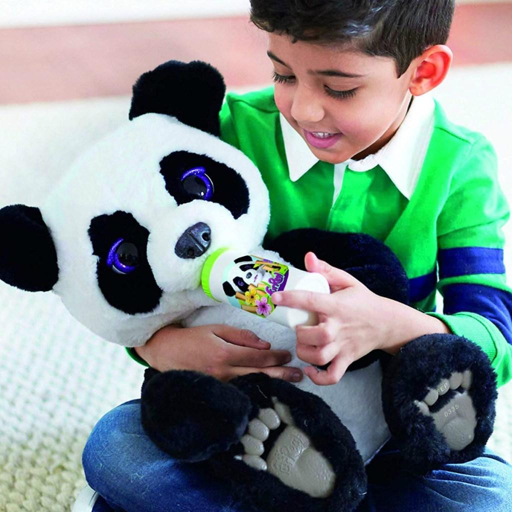 Boy holding interactive plush panda bear