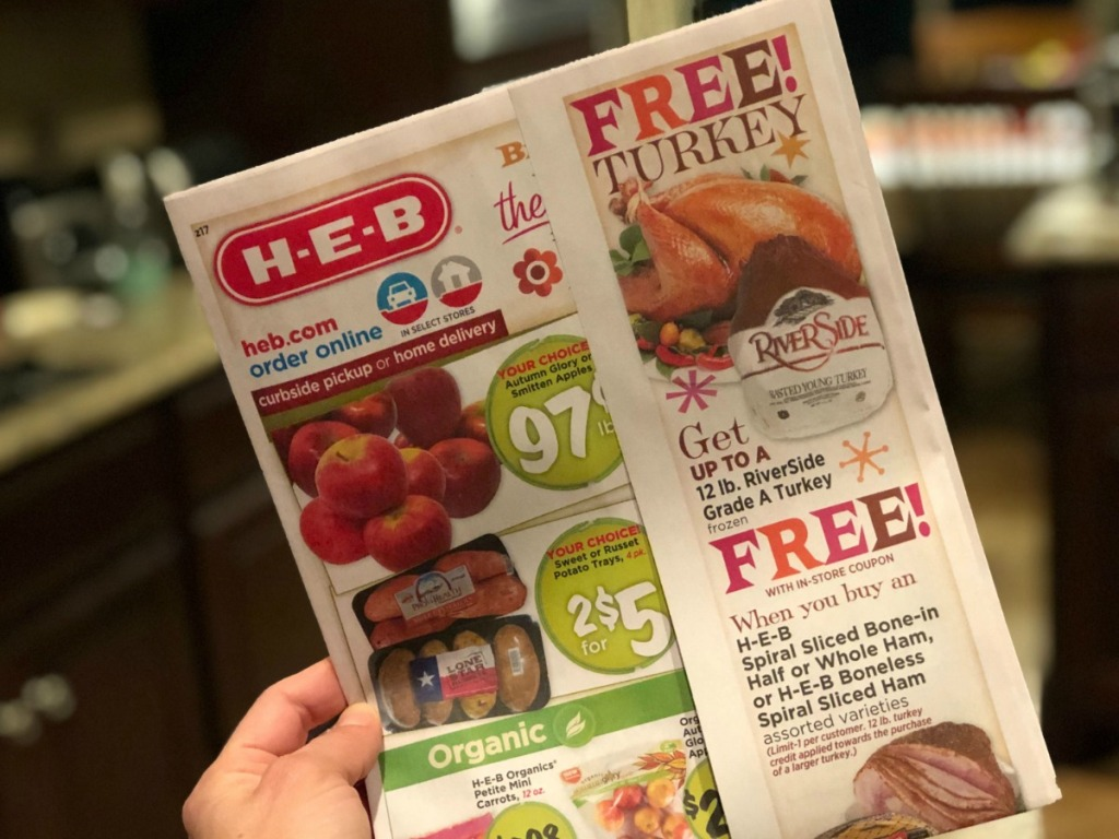 woman holding an HEB ad for a free turkey