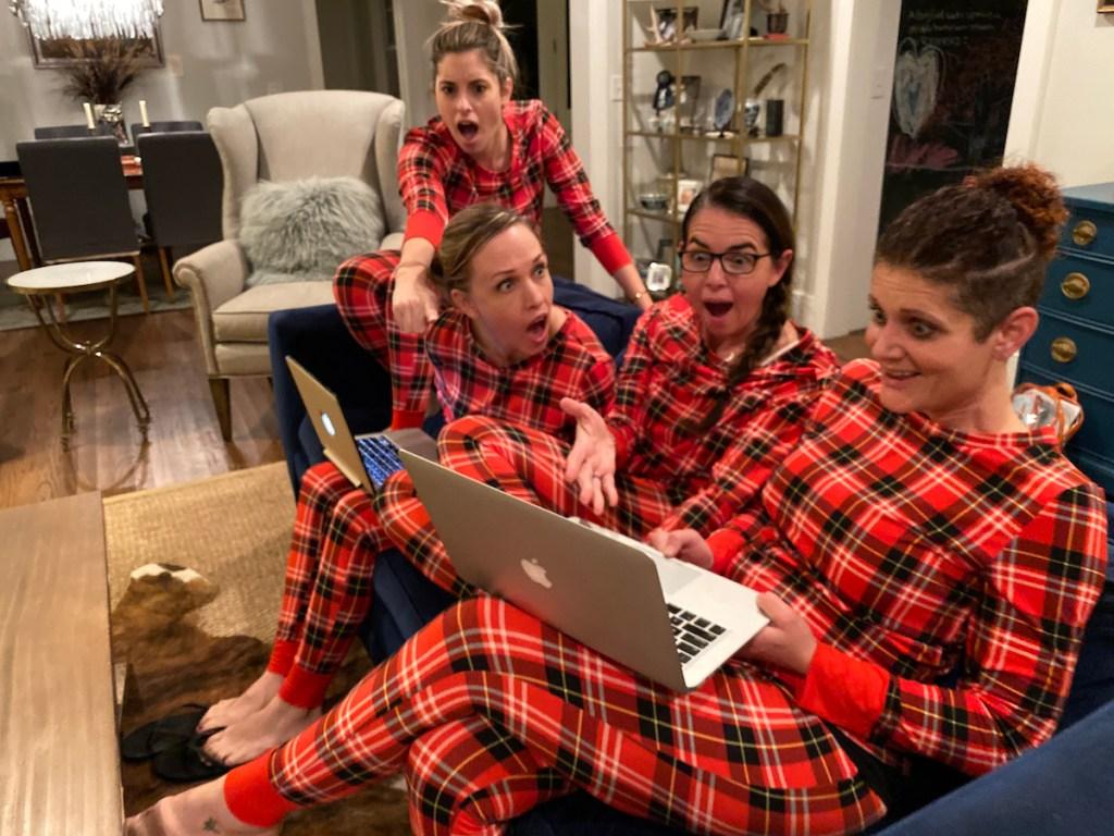 Women in matching pajamas staring at computer in surprise